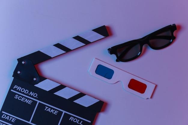 Доска с хлопушкой фильма с очками 3d в синем красном неоновом свете. киноиндустрия, развлечения. вид сверху
