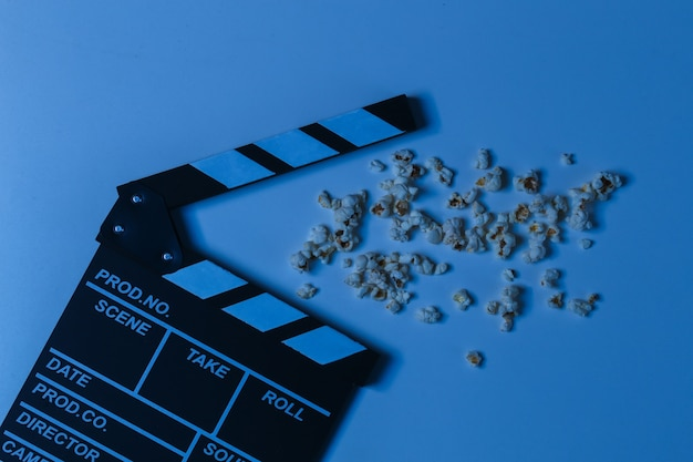 Film clapper board with popcorn in blue neon light. cinema industry, entertainment. top view