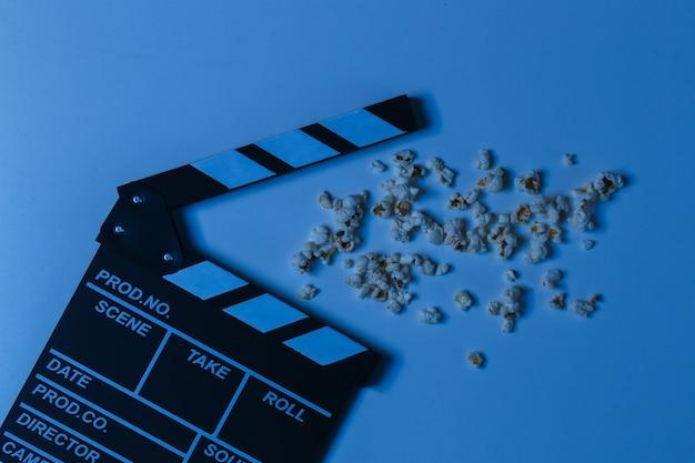 Доска с хлопушкой пленки с попкорном в синем неоновом свете. киноиндустрия, развлечения. вид сверху