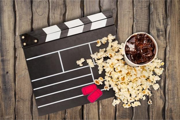 Фильм клипер, попкорн и лимонад в чашке на фоне деревянных досок. концепция времени фильма