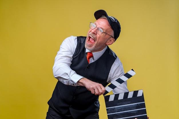 Режиссура фильма. производство фильмов. человеческие эмоции. человек с заслонкой фильма во время съемок. закройте вверх.