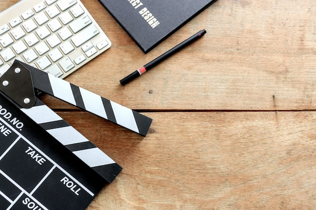 Film director's desk. clapboard, book and digital camera on wood table