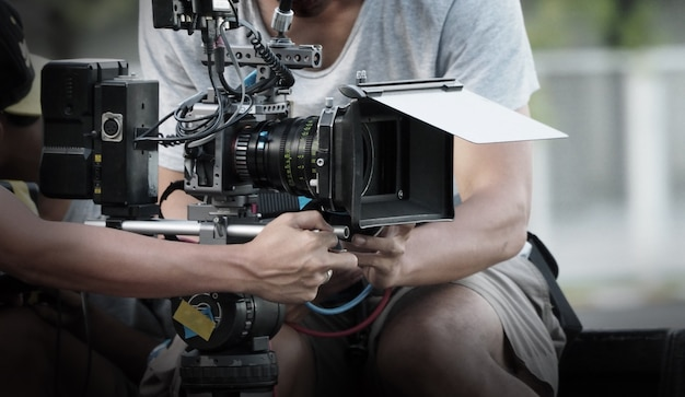 Film industry. filming with professional camera. videographer holding 4k cam on dslr rig or gimbal stabilizer set.