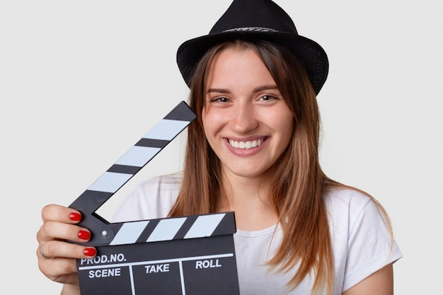 Film making concept. pleasant looking joyful woman wears hat, has broad smile, holds film slate or clapper board, being in good mood, spends time on movie set, isolated over white wall