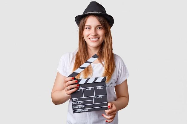 Film production concept. pleased caucasian female holds movie clapper