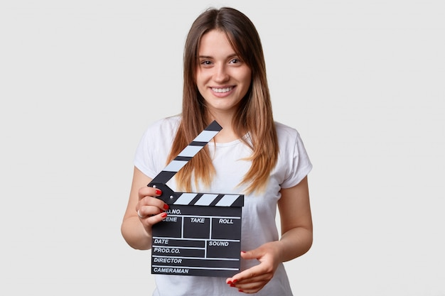 Film productivity concept. beautiful pleased smiling young woman holds moving clapper board