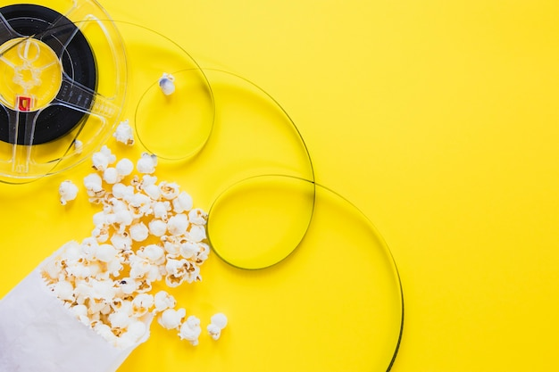 Film reel and popcorn on yellow