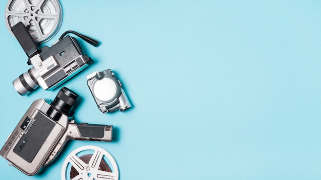 Film reel and various type of camcorder on blue background