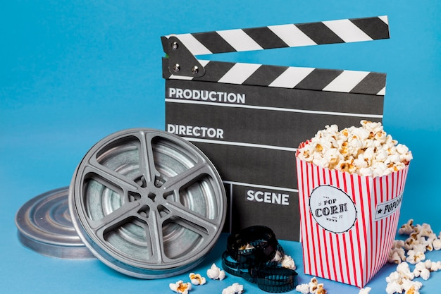 Film reels; film strips and clapperboard with popcorn box on blue background