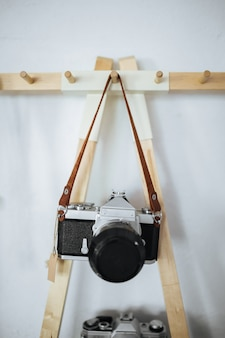 Film retro camera hanging on a strap on a white wall space