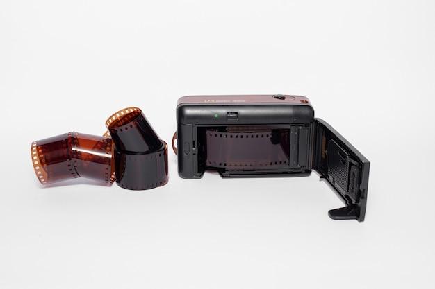 白い孤立した表面上のフィルムロールとオープンフィルムカメラ