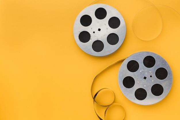 Rotoli di pellicola su sfondo giallo con spazio di copia