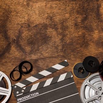 フィルムストライプフィルムリールと木製の机の上のカチンコ