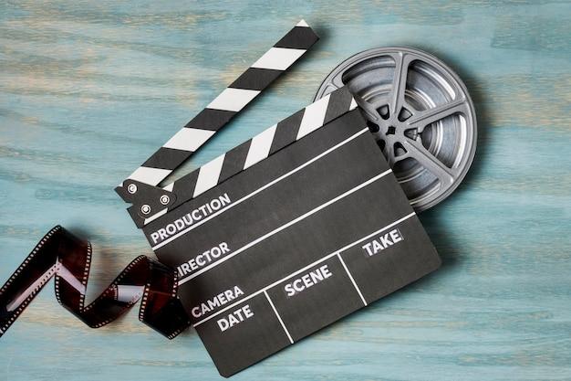カチンコと青の織り目加工の背景にフィルムリールのフィルムストライプ