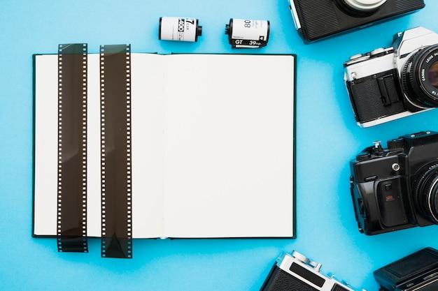 Strisce di pellicola su notebook vicino a fotocamere