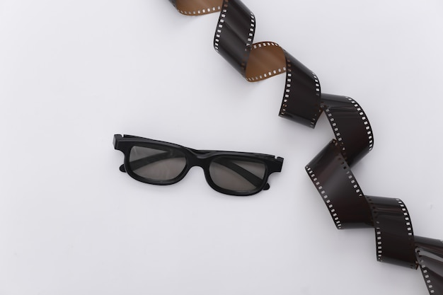 Film tape and 3d glasses on white background. ãâ¡inema, entertainment industry. top view