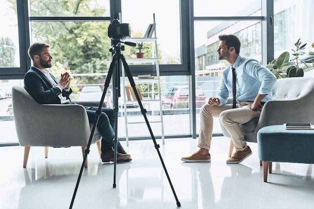 촬영 인터뷰. 스마트 캐주얼 차림의 두 젊은이가 실내에서 새 비디오를 만드는 동안 이야기하고 있습니다.