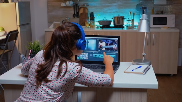 Filmmaker editing video footage during night time in home kitchen. creative videographer working on audio film montage on professional laptop sitting on desk at home in midnight.
