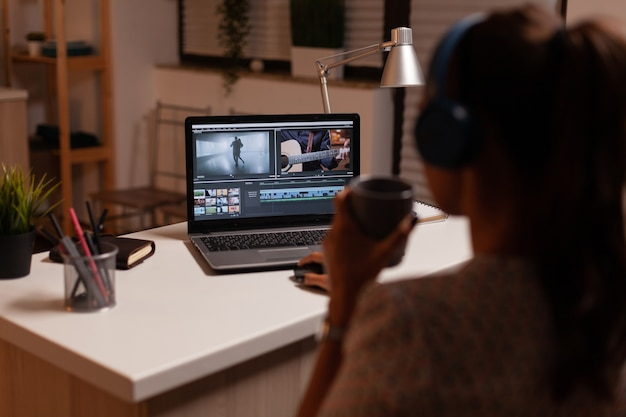 Filmmaker editing video footage during night time in home kitchen
