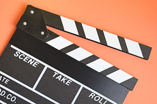 Filmmaker profession. clapperboard on ogange background top view.