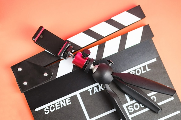 Filmmaker profession. clapperboard and tripod for phone