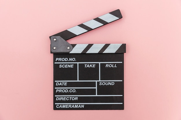 Filmmaker profession. classic director empty film making clapperboard or movie slate isolated on pink wall. video production film cinema industry concept. flat lay top view copy space .