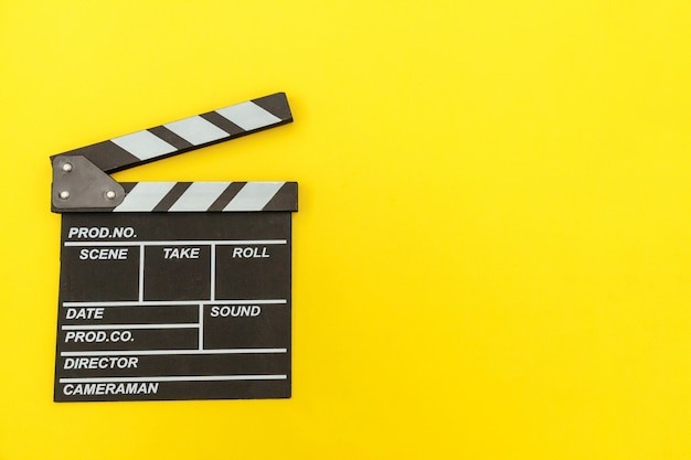 Filmmaker profession. classic director empty film making clapperboard or movie slate isolated on yellow. video production film cinema industry concept. flat lay top view copy space mock up.