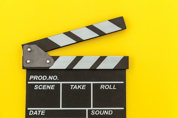 Filmmaker profession. classic director empty film making clapperboard or movie slate isolated on yellow wall. video production film cinema industry concept. flat lay top view copy space .