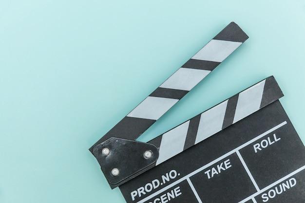 映画製作者の職業。カチンコや映画のスレートを作る青い壁に分離された古典的な監督の空の映画。ビデオ制作映画映画業界のコンセプト。フラット横たわっていたトップビューコピースペース。