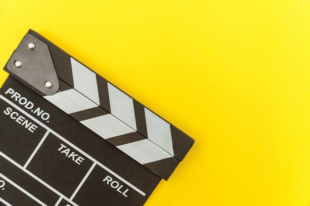 映画製作者の職業。古典的な監督の空の映画は、カチンコや映画のスレートを黄色の背景に分離します。ビデオ制作映画映画業界のコンセプト。フラットレイアウトトップビューコピースペースのモックアップ。