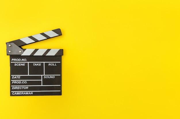 映画製作者の職業。黄色の壁に分離されたカチンコや映画のスレートを作る古典的な監督の空の映画。ビデオ制作映画映画業界のコンセプト。フラット横たわっていたトップビューコピースペース。