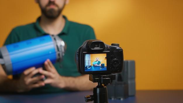 Режиссер записывает мнение о видеосвете и держит ее перед камерой. профессиональное студийное видео и фотооборудование для работы, звезда социальных сетей и влиятельный человек в фотостудии
