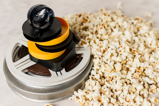 Filmstrip on yellow and black case over the movie film reel with popcorns