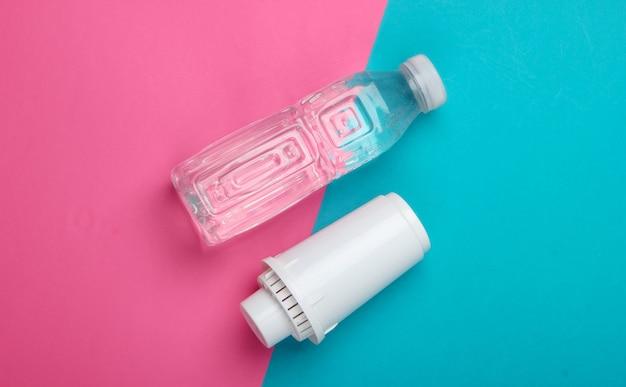ピンクブルーの背景に水フィルターと純水のボトルのフィルター要素。上面図