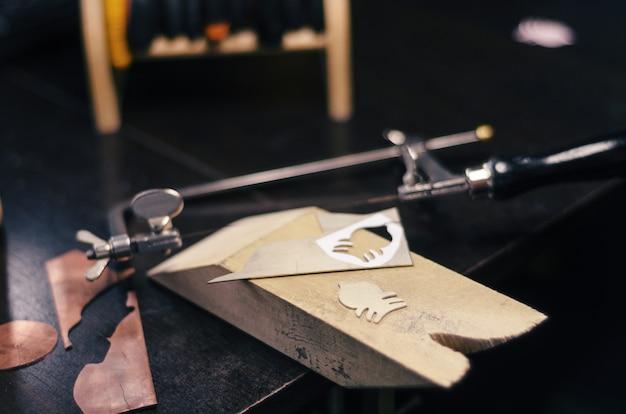 デスクトップテーブルの上の自家製ジュエリーのためのツール。ジグソー、金属、形、細部、finagel