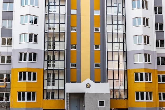 Завершающие строительные работы на фасаде нового многоэтажного жилого дома. сдача объекта в эксплуатацию.