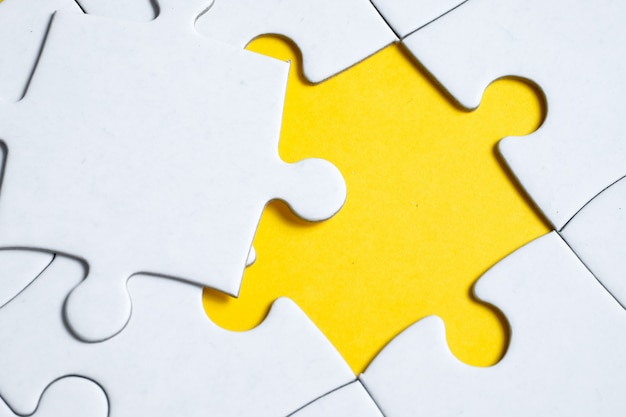 Final missing white piece lies on jigsaw puzzle on yellow .