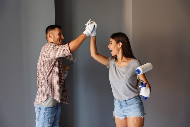 Окончательная покраска в новом доме. счастливая пара празднует конец картины с валиком на серой стене