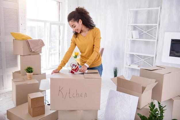 Final preparations. upbeat curly-haired girl smiling pleasantly and taping the box with kitchen utensils with an adhesive tape before moving out of the flat