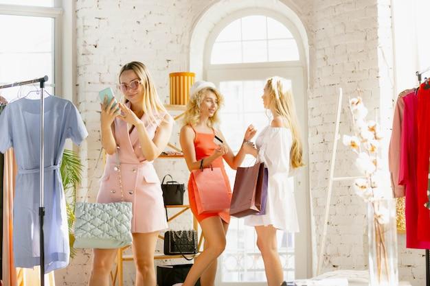 Последняя распродажа. одежда, магазин одежды во время распродаж, летняя или осенняя коллекция. молодые женщины ищут новую одежду. понятие моды, стиля, предложений, эмоций, продаж, покупок. совершенно новые покупки.