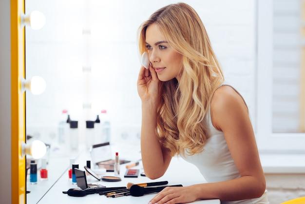 마지막 터치. 면 디스크를 사용하고 화장대에 앉아 거울에 비친 자신의 모습을 바라보는 아름다운 젊은 여성의 측면