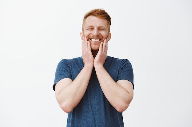 Наконец-то отрастила борода. довольный радостный счастливый красивый зрелый мужчина с рыжими волосами, трогающими щетину и широко улыбающийся с закрытыми глазами, находящийся на небесах от счастья и положительных эмоций