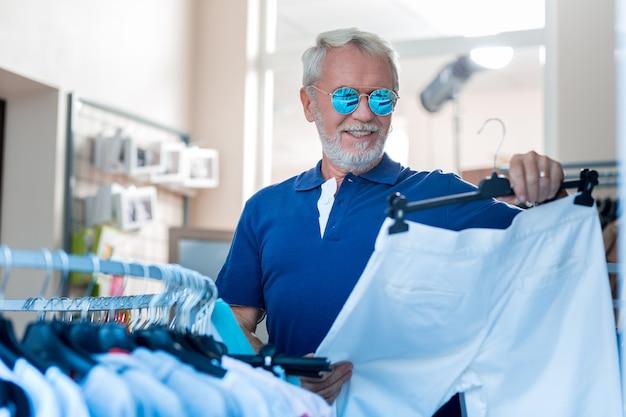 ついに見つけた。購入への関心を表明しながら、選択した白いズボンを見ている満足している白髪の男の肖像画