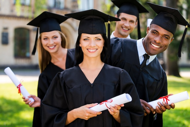Наконец-то закончил! четыре выпускника колледжа держат дипломы и улыбаются, стоя в ряд