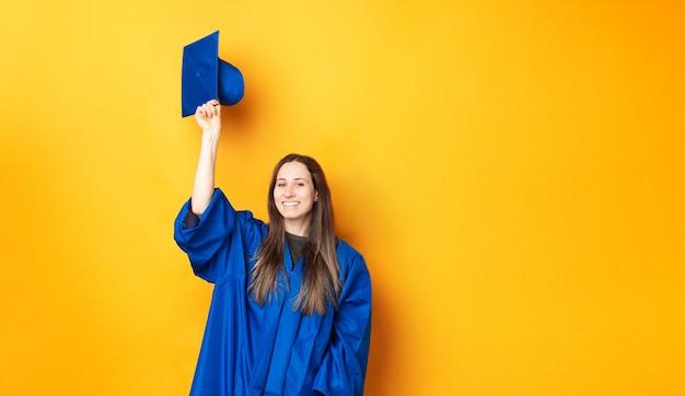 ついに卒業した若い女性は黄色の背景に笑みを浮かべています。