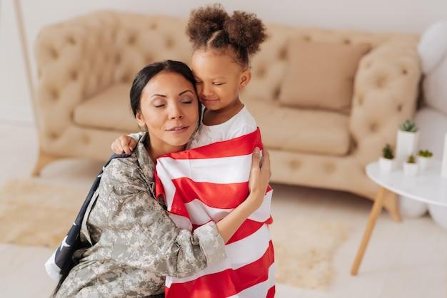 Наконец-то здесь с вами. сентиментальная нежная молодая женщина, тронутая приветствием дочери и крепко обнимающей ее после возвращения домой