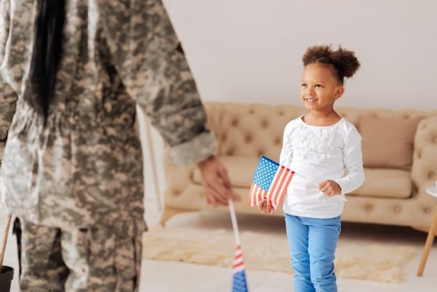 Наконец то дома. взволнованная жизнерадостная молодая девушка ждет возвращения мамы в гостиной, держа флаг и выглядит взволнованной