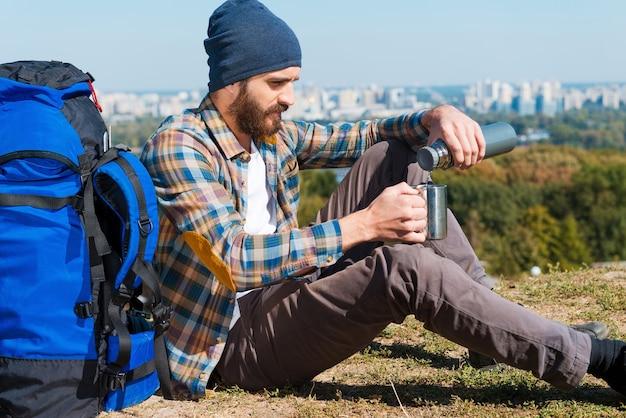 Наконец-то я могу расслабиться. красивый молодой человек сидит возле рюкзака и наливает чай в чашку