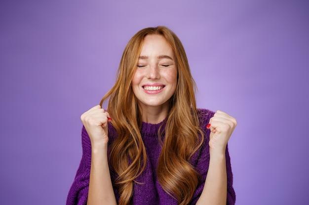 Наконец я победил. портрет радостной и счастливой торжествующей красивой рыжеволосой женщины, сжимающей кулаки от радости и счастья, празднующей победу и аплодирующей с закрытыми глазами и довольной улыбкой.