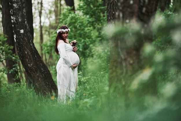 最後に、夏です。ドレスを着た美しい妊娠中の女性は、屋外散歩をしています。肯定的なブルネット